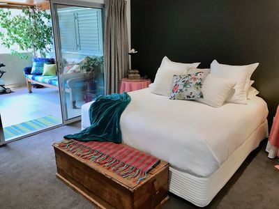 The king size bed has luxury linens and aaccess to the balcony