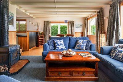 The cosy lounge room has a wood burning fireplace, a heat pump and comfy seating