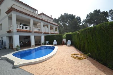 Completely fenced exterior with swimming pool, sun beds and outdoor shower.