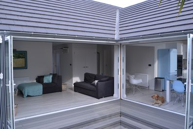 Lounge and Kitchen with Bi Fold Doors opening to the decking area and garden.