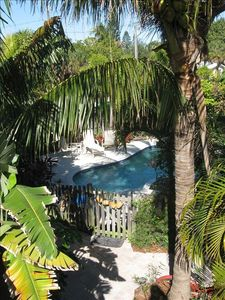 the view from the crows nest porch is of our tropical landscaping & pool