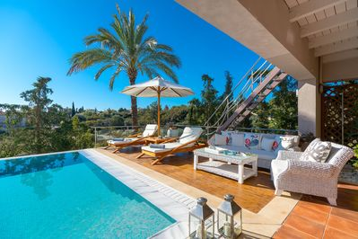 Sunbeds and sofa by the pool