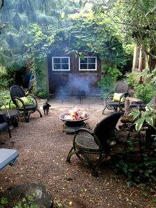 The view of the fire-pit and seating area around it. The barbecue is to the left