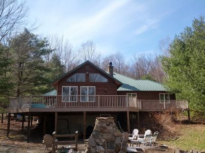 Front View, Large Deck, Patio Area with stone fire pit and charcoal grill.