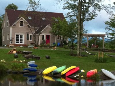 Summer view of the main house from the pond-- pergola, firepit, kayaks & hammock