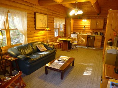 Living, dining, kitchen area, with vaulted ceilings, and hearth stove in corner.
