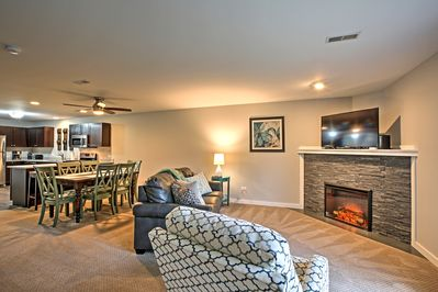 Warm your toes by the electric fireplace at this Utica vacation rental villa!