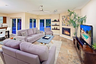 Bright and open living room with romantic fireplace and high definition TV