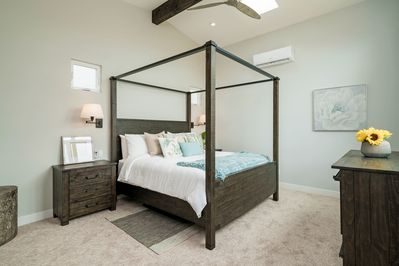 Spacious and bright master bedroom suite with an ocean view, AC, ceiling fan.