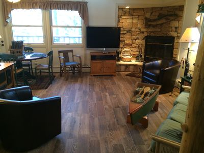 Flat screen TV, wood tile, fireplace.