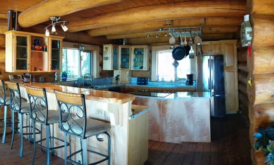 Large Kitchen with granite counter tops and bar with stools