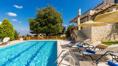 Spacious garden area with trees, flowers, swimming pool, sun beds, umbrellas etc