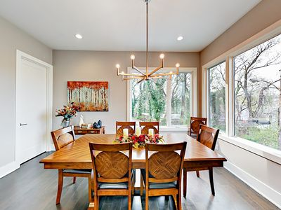 Dining Area - A modern chandelier hangs above the wood dining table.