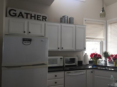 Clean, updated kitchen with gas stove, peninsula and large table with benches.