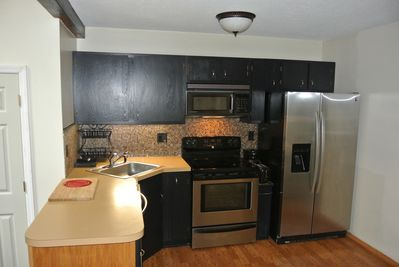 Kitchen with new dishwasher, oven/stove and refrigerator