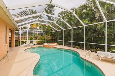 Free form swimming pool with spa and fully enclosed cage and lush landscaping