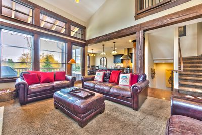 "Main level living room with gas fireplace, 55"" TV, and cozy seating"