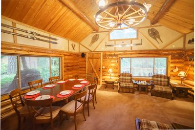 Main log cabin living room with large dining room table.