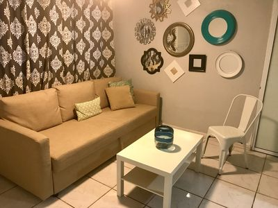 Cozy living room area with a queen size sofa bed. Open space area with kitchen
