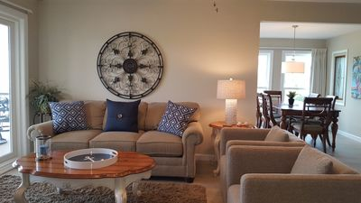 Seating group in living room with pull out sofa, 2 swivel arm chairs and deep pile area rug; partial view of dining room.