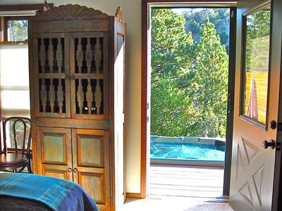 Door from master bedroom to deck and hot tub on the river in summer.