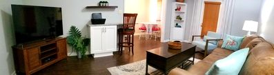 Living room has wrap around bar to kitchen with bar stools for extra seating.