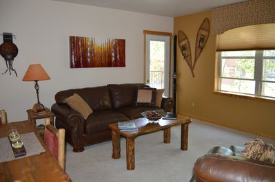 Living room has a pull out leather  sofa.