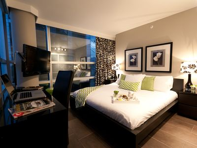 King-size bed with luxurious linen, ceiling to floor windows, black-out drapes.