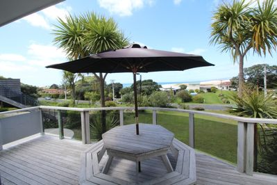 Sea facing deck with large outdoor table and umbrella