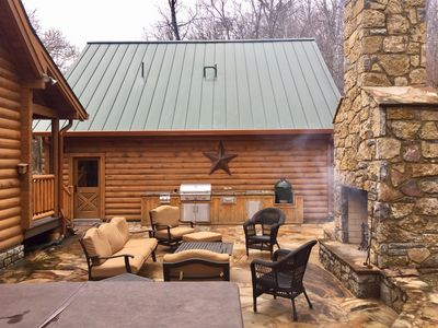 Outdoor stone patio w/ kitchen, fire place & hot tub