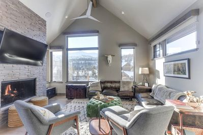 Large living room with motorized shades and views of ski resort.