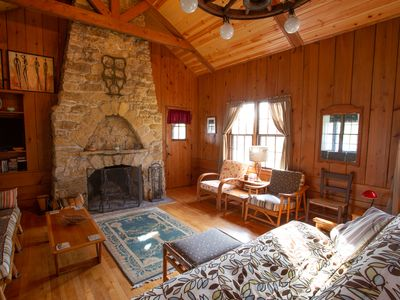 Classic cabin/cottage with big screen porch, stone fireplace, knotty pine walls.