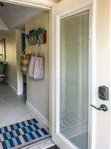 Front door entry (Mini blinds inside of dual, impact glass window panes)