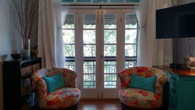 Plush, custom made chairs swivel 360 degrees & French doors open to the balcony.