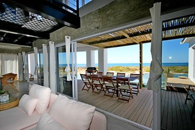 Large glass sliding doors open to a spacious verandah with views toward the sea