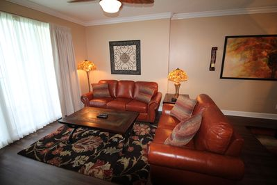 Spacious living area with brand new leather sofa and love seat.