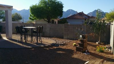 back yard view of Catalina mountains.  Tall table set, fountain & palm tree