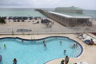 Pool, fishing pier with restaurant, and beach view from gym