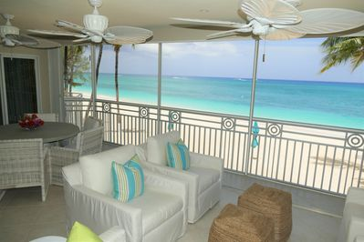 Spacious Screened Porch with dining table, 4 club chairs, and love seat