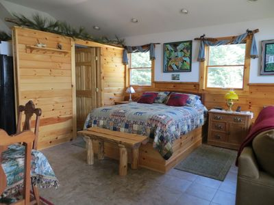 Queen pillow-top with rustic quilt and custom log bench.