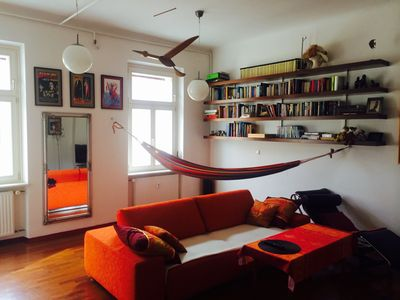 the living room with a hammock, books and a bird to watch over you