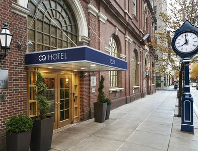 CQ hotel main street side entrance showing brick facade and large curve top windows.