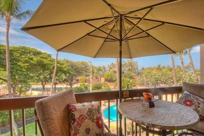 Lanai with large shade umbrella, view of pool and ocean.