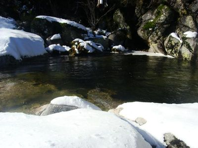 river with snow near the house