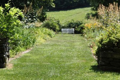 Seating at the end of the walled garden looking back on the house