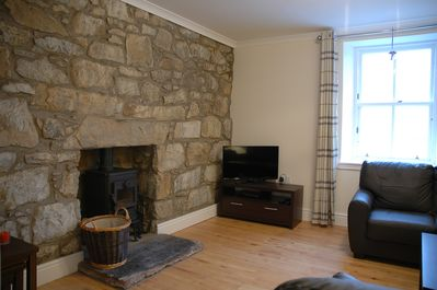 Lounge with exposed stone fireplace and wood burning stove