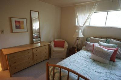 Bedroom has plenty of storage space, an armchair and large mirror.