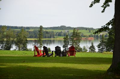 Peaceful scene as you pull up the driveway.  Adirondack chairs at fire pit.