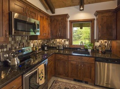 Abundantly equipped modern kitchen, granite counters, glass tiles & stainless.