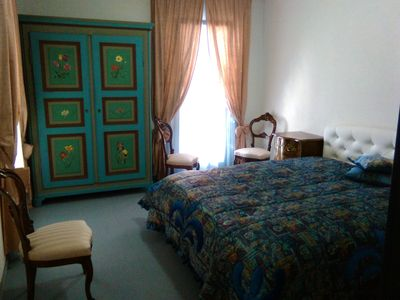 Finely furnished private double room with a king bed, bedside tables, beautiful art- wardrobe and chairs